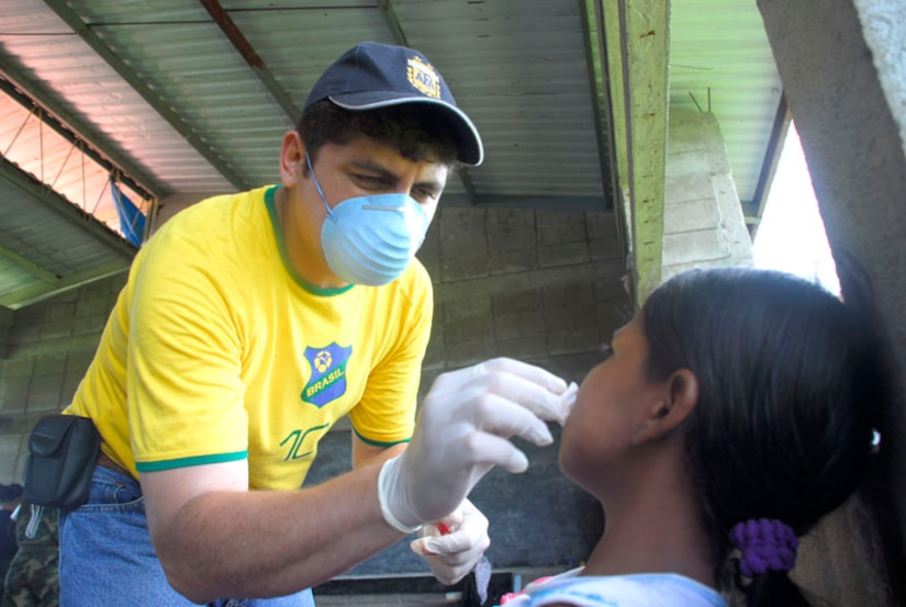 CLUBKI, Honduras - Dr. Juan Alejandro Burgos pulls a tooth from a young child Aug. 19 in a medical readiness exercise here. Dr. Burgos is part of a multi-national team that came to the La Mosquita region to train for a medical disaster and help the people in these villages. (U.S. Air Force photo by Staff Sgt. Joel Mease)