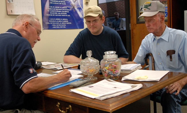 Retired Senior Master Sgt. Joe Wheeler, Little Rock Air Force Base Retiree Activities Office assistant, reviews documents with Damon Poole II, center, and retired Air Force Master Sgt. Damon Poole, right.(U.S. Air Force photo by Senior Airman Chris Willis)