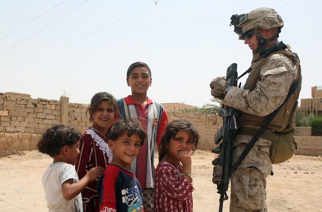Petty Officer 3rd Class Andrew Harang, senior corpsman with Company C, Task Force 1st Battalion, 2nd Marine Regiment, Regimental Combat Team 5, bonds with children in Habbaniyah, Iraq, a major city in the battalion's former area of operations. The battalion recently completed the movement from RCT-1's area of operations and plans to continue its mission to facilitate a sustainable Iraqi infrastructure in Rawah, Iraq.