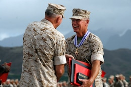 Lt. Gen. John F. Goodman, (right) commander, U.S. Marine Corps Forces, Pacific, shakes hands with Gen. James T. Conway, (left) Commandant of the Marine Corps, after receiving awards during his change of command and retirement ceremony on the flightline here Aug. 22.