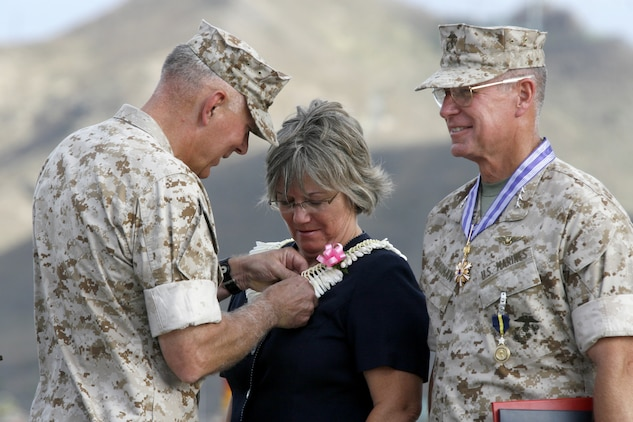Gen. James T. Conway, (left) Commandant of the Marine Corps, presents Gayle Goodman, wife of Lt. Gen. John F. Goodman, (right) commander, U.S. Marine Corps Forces, Pacific, with a Superior Public Service Award during her husband's change of command and retirement ceremony on the flightline here Aug 22.