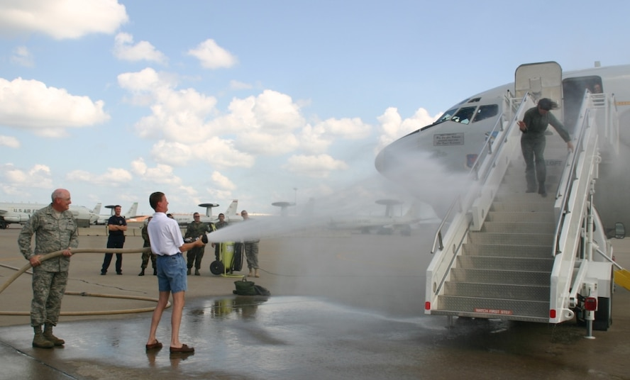 Brig. Gen. Lori Robinson, commander, 552 Air Control Wing,  is blasted with water by her husband, Maj. Gen. (Ret) David Robinson and Maj. Gen. Loren Reno, commander, Oklahoma City Air Logistics Center, during the traditional celebration of her final flight on the E-3 Sentry as her role as the commander of the 552 ACW comes to an end. After being soaked by the fire hose, hundreds of 552 ACW Airmen congratulated her with super soakers and champagne! (Photo courtesy of 2nd Lt. Kinder Blacke)