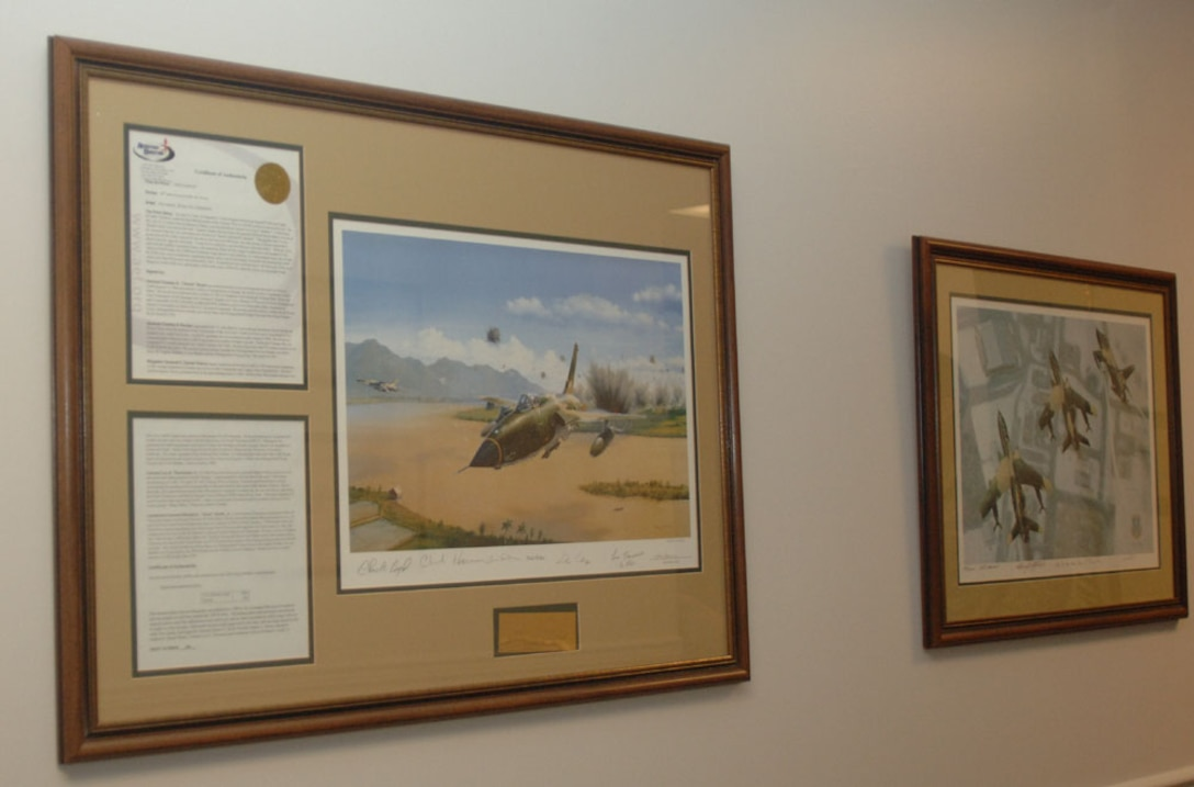 """The artwork """"Thud Ridge"""" portrays the F-105D in the first official attack of the Vietnam War. This print is signed by past members of the 50th Flying Training Squadron to include Lt. Col. Richard """"Gene"""" Smith, Jr. of which the plaza at Columbus AFB is named after. (U.S. Air Force photo by Senior Airman Danielle Hill)"""