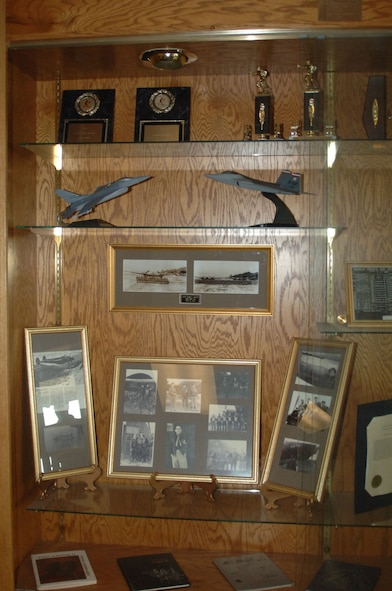 One of the many displays throughout the hallways of the 50th Flying Training Squadron containing pictures of old squadron members and trophies won. Lt. Col. Youngsworth is depicted in the picture frame directly beneath the air craft models. These pictures are part of the Youngsworth collection. (U.S. Air Force photo by Senior Airman Danielle Hill)