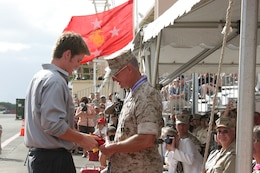 Michael Goodman (left) passes a three-star flag to his father, Lt. Gen. John F. Goodman at the flightline here Aug 22.  Goodman relinquished command of U.S. Marine Corps Forces, Pacific and retired after 41 years of military service.