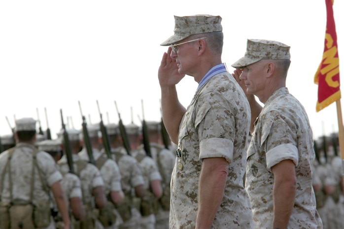 Lt. Gen. John F. Goodman, (left ) outgoing commander, U.S. Marine Corps Forces, Pacific, and Brig. Gen. Rex C. McMillian, (right) deputy commanding general, MarForPac, salute units as they pass during Goodman?s change of command and retirement ceremony at the flightline here Aug. 22.