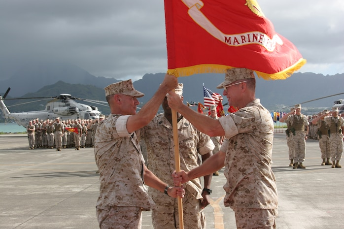 Lt. Gen. John F. Goodman, (right) commander of U.S. Marine Corps Forces, Pacific passes the Marine colors to Brig. Gen. Rex C. McMillian, (left) deputy commanding general, MarForPac during a change of command and retirement ceremony on the flightline here Aug. 22.