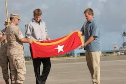 (From left to right) Capt. Jeff Goodman, Michael Goodman and John Goodman II, sons of Lt. Gen. John F. Goodman, commander, U.S. Marine Corps Forces, Pacific, fold their father's three-star flag during the MarForPac change of command and reitirement ceremony.  Their father also retired after 41 years of military service.
