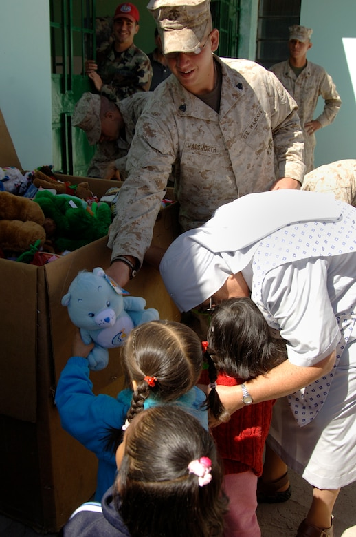 U.S. Marine Sgt. Danial Wadsworth, a vehicle maintainer with Task Force New Horizons, gives a toy to a Peruvian girl at the Juan Andres Vivanco Amorin Orphanage in Ayacucho, Peru, Aug. 14.  Task froce members visited the orphanage to bring toys collected by the 472nd Marine Wing Support Squadron at Willow Grove, Pa., and to spend the morning playing with the children.  More than 950 servicemembers deployed to Ayacucho, Peru to support New Horizons - Peru 2008, a U.S. and Peruvian humanitarian effort to bring quality-of-life construction projects and medical missions to impoverished Peruvians. (U.S. Air Force photo/1st Lt. Mary Pekas)