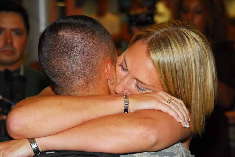 Tech. Sgt. Jose De Jesus is hugged by his wife Monique. All 19 of the 162nd Fighter Wing's Security Forces members returned home safely Aug. 23 after six months in Iraq. (Air National Guard photo by Master Sgt. Dave Neve)