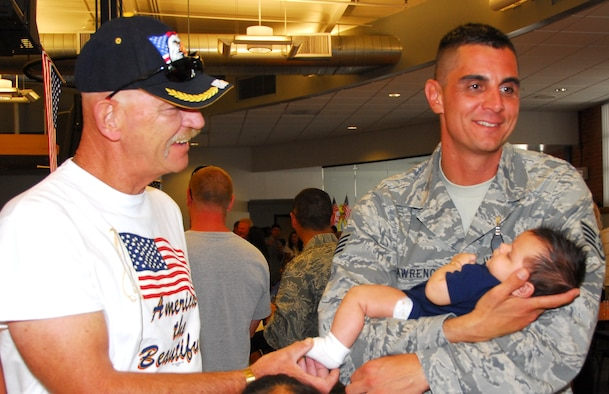 Staff Sgt. Dan Lawrence meets his son Ryan for the first time while his father Chief Master Sgt. (Ret.) Dan Lawrence looks on. All 19 of the wing's Security Forces members returned home safely Aug. 23 after six months in Iraq. (Air National Guard photo by Master Sgt. Dave Neve)