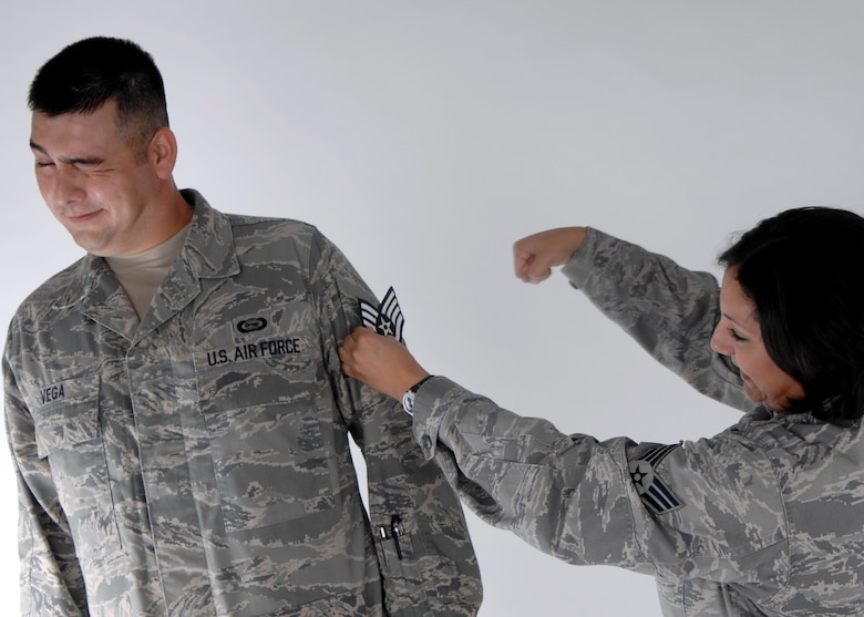 Senior Airman Sonia Vega tacks on her husband, Senior Airman John Vega's new staff sergeant stripes after the promotion results were released Aug. 20.  The Senior Airmen Vegas were high school sweet hearts who have been married for more than four years and have two sons. (U.S. Air Force photo by Airman 1st Class Joanna M. Kresge)