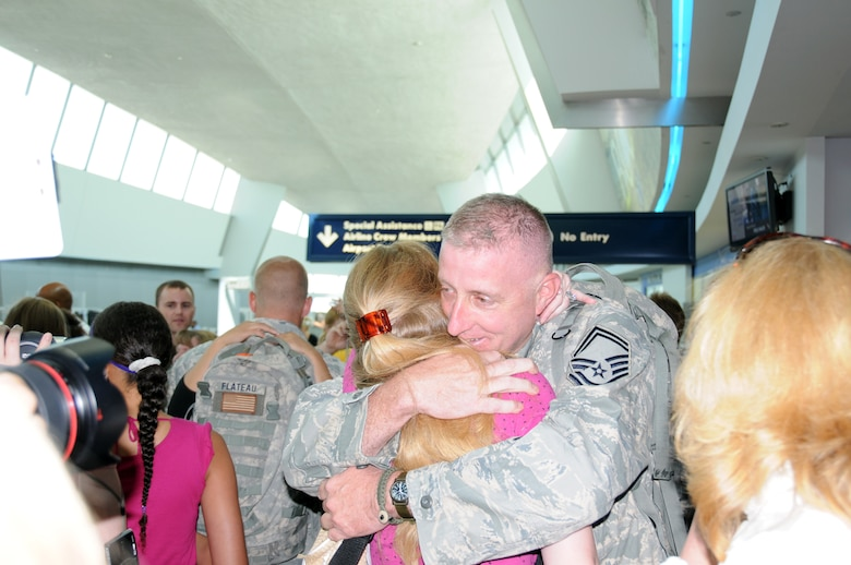 Senior Master Sgt. Paul Wiencek and his daughter embrace for the first time in six months. The sergeant and other members of the New York Air National Guards 107th Airlift Wing Security Forces Squadron just return home from Iraq after a six month deployment.(US AirForce photo/SrA Peter Dean)