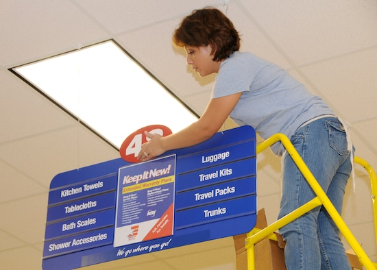 ANDERSEN AIR FORCE BASE, Guam - Ballen Chambers hangs an aisle sign inside the new base exchange here Aug. 26. The new BX opens Sept. 10 at 9 a.m. The new BX is open seven days a week from 9 a.m. to 8 p.m. and from 10 a.m. to 6 p.m. on holidays. (U.S. Air Force photo by Airman 1st Class Courtney Witt)
