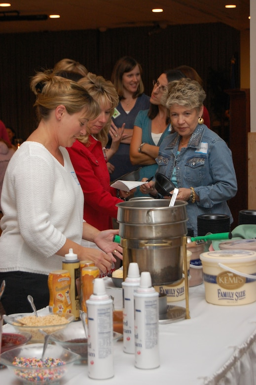 Diana Kelch, Julie Dodge and Sharon Gotcher dig in to the ice cream during the Malmstrom Spouses Club Ice Cream Social at the Grizzly Bend Club Aug. 21. The social was held to give members and non-members a chance to socialize and see what the MSC has to offer. More than 50 spouses were in attendance. (U.S. Air Force photo/Senior Airman Emerald Ralston)