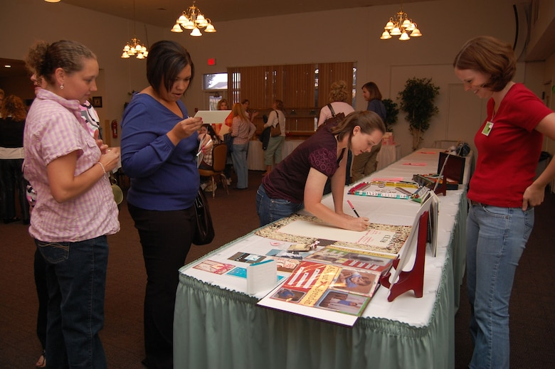 Brittney Leverett mans the scrapbooking display as Leanne Ward, Abbie Chalupnik and Bonnie Miller sign up to join the scrapbooking group during the Malmstrom Spouses Club Ice Cream Social Aug. 21 at the Grizzly Bend Club. The social was held to give members and non-members a chance to socialize and see what the MSC has to offer. More than 50 spouses were in attendance. (U.S. Air Force photo/Senior Airman Emearld Ralston)