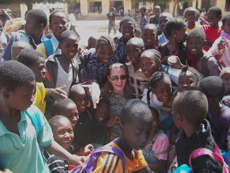1st Lt. Lauren Johnson is surrounded by a group of African children recently at a school outside the airport in Bamako, Mali. Lt. Johnson was in Africa supporting FLINTLOCK, a training exercise featuring the United States and 15 African and Partner Nations designed to increase security and build capacity in the Trans-Saharan region. (U.S. Air Force photo/1st Lt. Jon Saas)
