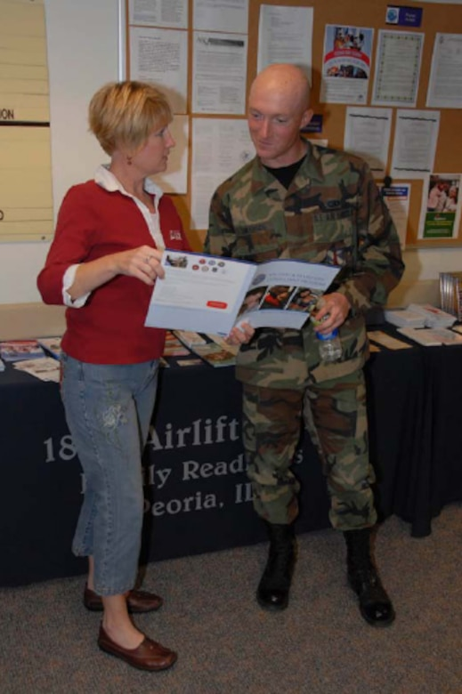 Susan Webb, President of the 182nd Airlift Wing Family Readiness Group, discusses some resources available to military members and their families to Senior Airman Scott Swanson, from the Communications Flight. Photo by Tech. Sgt. Shane Hill