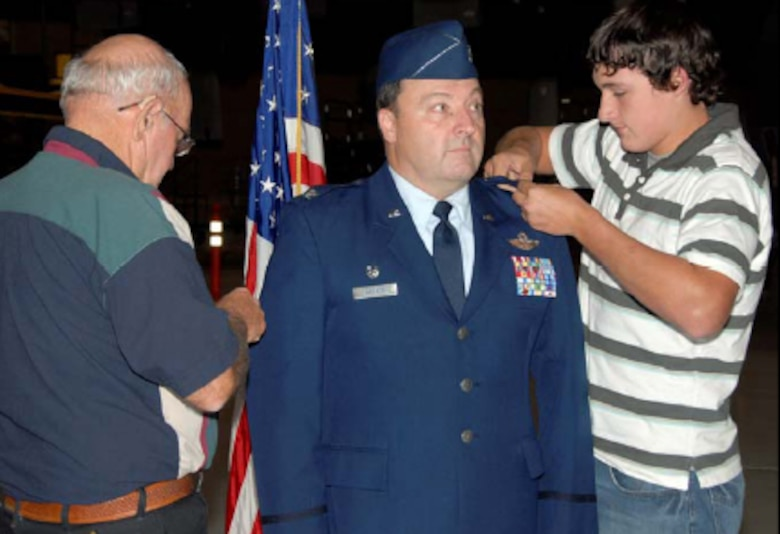 Lt. Col. Bart Welker, 182nd Maintenance Group Commander receives his Colonel's eagles from father, Mr. Don Welker, and son, Brodie Welker during a short ceremony that took place here, in the main hangar, Nov. 2.
