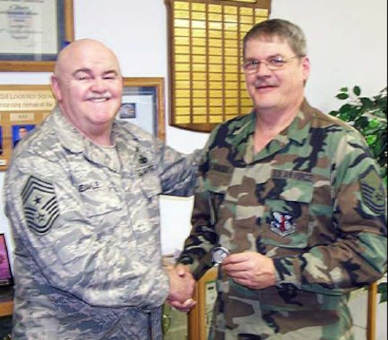 """Senior Master Sgt. Steve Schneider receives a Chief's coin from Command Chief Master Sgt. Steve Eakle for his participation in the annual 182nd Airlift Wing bowling tournament. This was the 25th year for the tournament.   Schnieder has been coordinating the event for the last five years, but assisted retired Master Sgt. Karl Cooper for the preceding 15 years. He enjoys coordinating the tournament because it gives him a chance to meet and see people from all the squadrons on base. A causal bowler himself, he only bowls occasionally and doesn't belong to any leagues.  He feels the tournament is a success because """"the bowlers in the tournament do a great job of watching out for each other, and has always been a fun event."""" This year the tournament had 215 bowlers and occupied 43 lanes at Landmark Lanes in Peoria."""