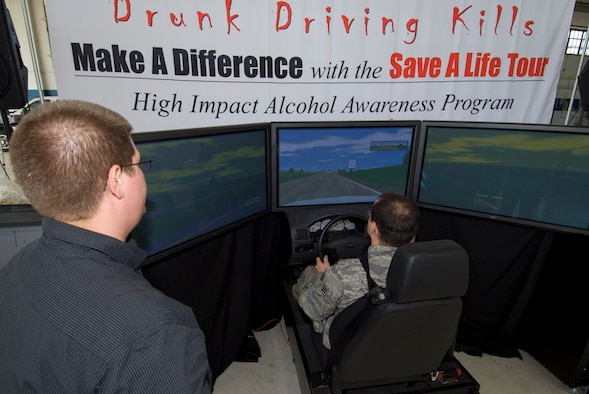 With the guidance of Jordan Brinks, Save A Life Tour simulator instructor, Staff Sgt. Jonathan Early attempts to navigate a driving scenario as if he's under the influence of alcohol Thursday. The Save a Life Tour began when Mr. Brinks, along with his team, began touring military installations to educate Airmen on the effects of alcohol. (Air Force photo by Jamie Pitcher)
