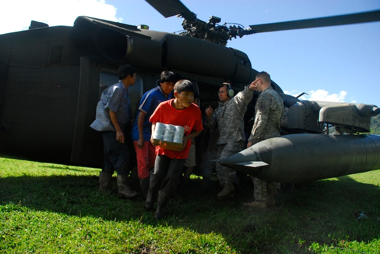 Army Staff Sgt. Samuel Colon directs locals from a remote village in Costa Rica where to pick up food from the Blackhawk helicopter Dec. 1. (U.S. Air Force photo by Staff Sgt. Joel Mease)