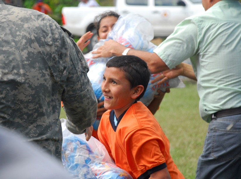 A child hands a bag of food to Army Specialist Ethan Anderson Dec. 1 at a food staging point near Puerta Limon, Costa Rica. (U.S. Air Force photo by Staff Sgt. Joel Mease)
