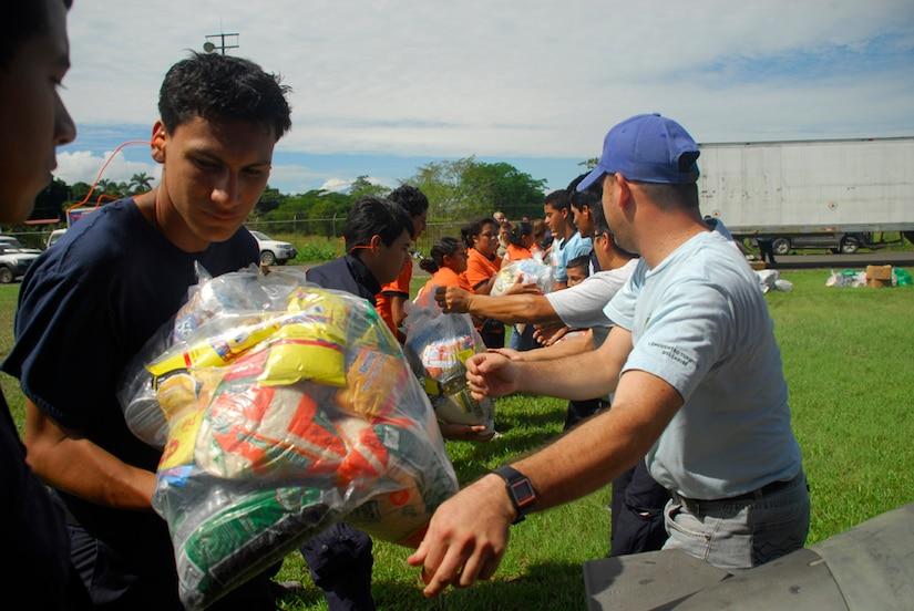 Members from the Costa Rican National Emergency Commision and Red Cross form a chain to load food onto a Blackhawk helicopter Dec. 1. More than 69,000 pounds of food and supplies had been delivered by Nov. 30. (U.S. Air Force photo by Staff Sgt. Joel Mease)
