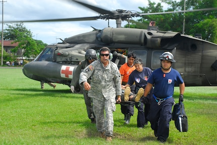 Army Staff Sgt. Jose Gutierrez and Specialist Robert Hunt carry an injured man from a medivac helicopter Dec. 1. More than 60 JTF-Bravo personnel participated in humanitarian disaster relief missions in Costa Rica and Panama. (U.S. Air Force photo by Staff Sgt. Joel Mease)