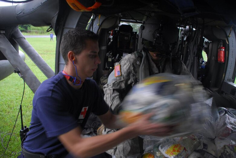Army Specialist Robert Hunt, Joint Task Force-Bravo crew chief, assists a member of the Costa Rica Red Cross load food onto a Blackhawk Nov. 30. (U.S. Air Force photo by Staff Sgt. Joel Mease)