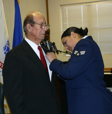 Senior Airman Crystal Garza proudly pins the Purple Heart on her grandfather, Mr. Hilario Riojas, during the official Purple Heart Ceremony in his honor November 26.