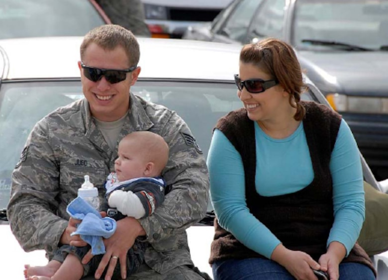 Staff Sgt. Bradley Judd of the 182nd Maintenance Squadron is joined by his wife Nichole and his five-month old son Payton shortly after arriving back in Peoria Oct. 14. The returning group of aircrew, maintainers, and other support personnel had departed for the 182nd Airlift Wing's first rotation of the Air Expeditionary Force (AEF #1) August 23. Photo by Tech. Sgt. Todd A. Pendleton