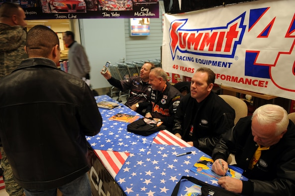 Four drivers from the National Hot Rod Association sign autographs and talk to servicemembers at the Vogelweh Base Exchange, during a USO sponsored trip, Ramstein Air Base, Germany, Nov. 25, 2008. The drivers are on the second leg of their trip after coming from Kuwait to visit American service members early that morning. (Airman 1st Class Scott Saldukas)
