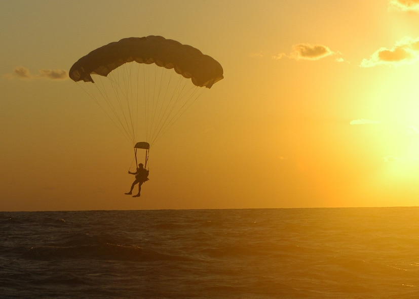 KADENA AIR BASE, Japan -- A pararescueman from the 320th Special Tactics Squadron prepares to land in the ocean  after jumping from a 1st Special Operations Squadron MC-130H Combat Talon II here Dec. 2.  The pararescueman was one of seven 320th STS members that parachuted into the water to search for survivors of a simulated aircraft accident. The event was part of a 353rd Special Operations Group training exercise testing the group?s ability to conduct search and rescue operations from start to finish. (U.S. Air Force photo by Tech. Sgt. Aaron Cram)