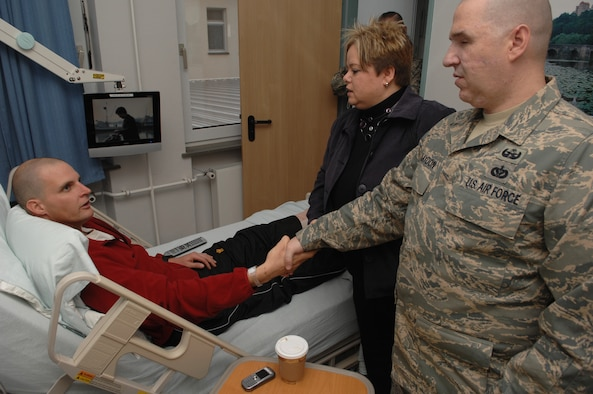 Canadian Army Corporal Robbie Stephenson (left), injured by an improvised explosive device blast during a convoy while deployed in Afghanistan, is visited by Staff Sgt. Matthew Slaydon and his wife, Annette, Landstuhl Regional Medical Center, Germany, Nov. 21, 2008. Sgt. Slaydon was severely injured in Iraq 13 months ago during a deployment there as an explosive ordinance disposal technician and is visiting LRMC as part of a morale tour, following his recovery. (U.S. Air Force photo by Airman 1st Class Tony R. Ritter)