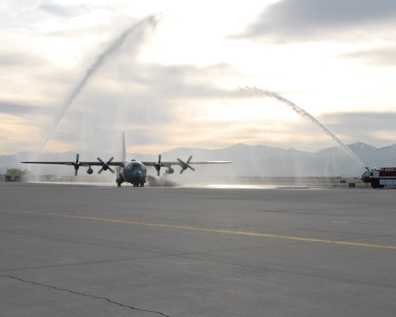 """A Minnesota Air National Guard C-130 """"Hercules"""" passes under a water-gun salute by the Utah Air National Guard fire department.  The plane carried 22 members of the 151st Security Forces Squadron who were returning home after being deployed to the Kingdom of Saudi Arabia for more than six months.U.S. Air Force photo by Staff Sgt. Emily Monson"""