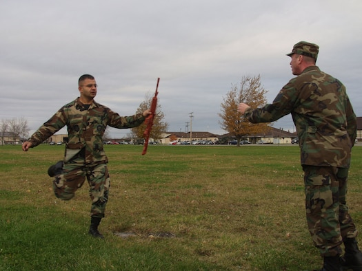 NIAGARA FALLS AIR RESERVE STATION, N.Y. --  Tech. Sgt. Mohammad Ali (left) hands off a training weapon to a fellow Airman during a skills challenge relay race here Nov.1, 2008.  (U.S. Air Force photo by Airman 1st Class Andrew Caya)