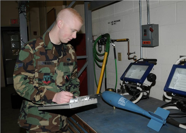 Airman Edwards inspects the serial number off a practice bomb.  Photo by Master Sgt. Mark Fortin