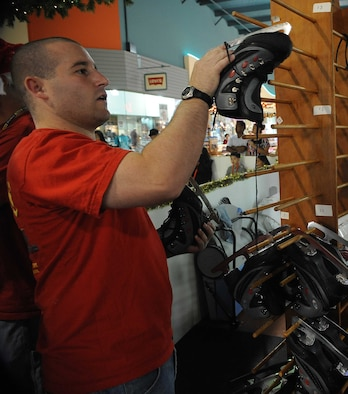 1st Lt. James Carmichael, 23rd Expeditionary Bomber Squadron, Andersen Air Force Base, Guam inspects ice skates on Dec. 6 during a fund raising event for Habitat for Humanity in downtown Guam. Airmen deployed to Andersen are contributing their time off to volunteer for Guam?s first ?ice? skating rink. The rink, which is a part of ?The Magic of Snow and Ice,? is located in the Guam Premier Outlets, and costs 5 dollars per person, with all proceeds going to the Habitat for Humanity.   Lieutenant Carmichael is deployed to Andersen, from Minot AFB, N.D.