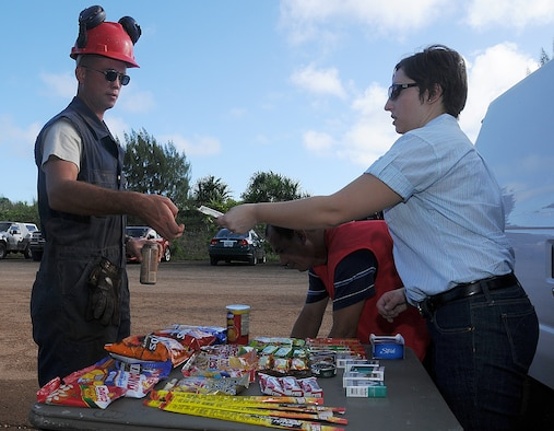 "ANDERSEN AIR FORCE BASE, Guam - Laurie Parker gives Staff Sgt. Dereck Ross, 554th REDHORSE Squadron, his change after he makes his purchase from the  ""mini shopette""  at Northwest Field on Dec. 5 here.   Army Air Force Exchange Service employees like Laurie, drive out to NWF on their days off to provide Airmen snacks and beverages before reporting to their work sites.  (U.S. Air Force photo by Staff Sgt. Jamie Lessard)"