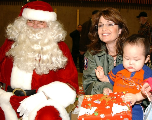 Wearing an Alaska Air National Guard flight jacket presented to her by Lt. Gen. (Alaska) Craig Campbell, adjutant general of the Alaska National Guard, Gov. Sarah Palin helps Santa pass out gifts during Operation Santa Claus 2008 in Kivalina Dec. 6. Operation Santa Claus, an Alaska National Guard community relations and support program, provides toys, books and school supplies for young people in communities across the state. Army National Guard photo by Spc. Paizley Ramsey, 134th Public Affairs Detachment.