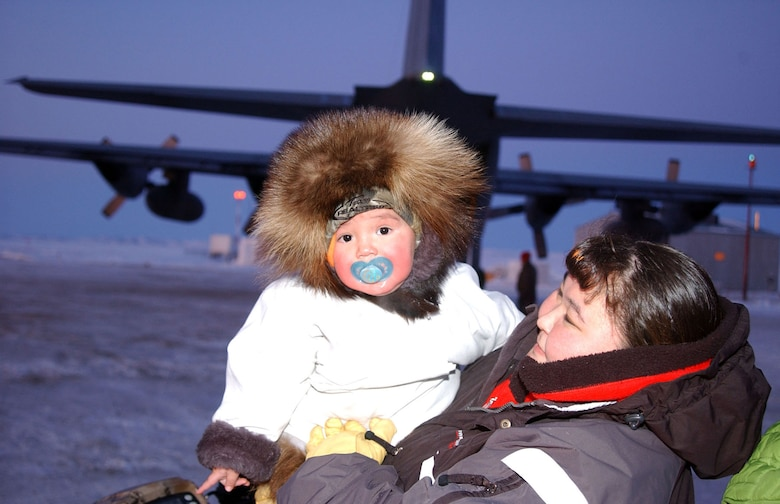 At the end of a successful Operation Santa Claus visit Dec. 6, this Kivalina mother and daughter team help National Guard members load a C-130 belonging to the Alaska Air National Guard's 144th Airlift Squadron. Operation Santa Claus, an Alaska National Guard community relations and support program, provides toys, books and school supplies for young people in communities across the state. Army National Guard photo by Spc. Paizley Ramsey, 134th Public Affairs Detachment