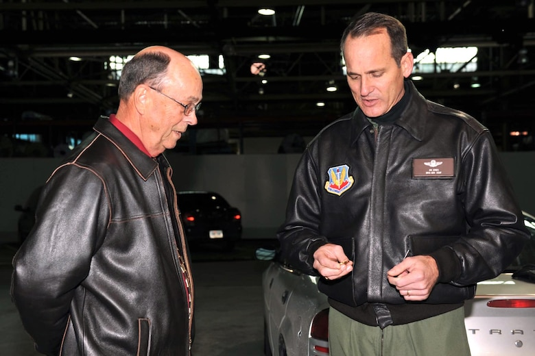 OFFUTT AIR FORCE BASE, Neb. -- Brig. Gen. James Jones, 55th Wing commander presents a coin to Mr. Cecil Weeks, 55th Civil Engineer Squadron chief of operations and mainitenance, Dec. 4 for his work spearheading the cleanup effort in the Martin Bomber Building. The building has undergone extensive cleanup efforts since March in order to improve the work environment for many military and civilian members of Team Offutt. This historic building consists of 1.5 million square feet and was used as a plant for B-26 Marauder Bombers and B-29 Superfortress Bombers during World War II.   (U.S. Air Force Photo By Charles Hammond)