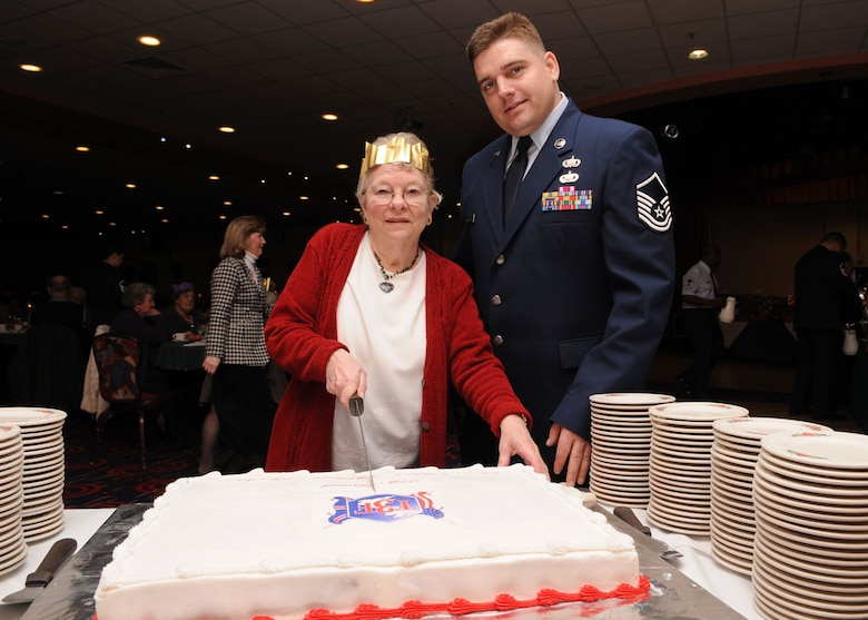Master Sgt. David Caruthers from the 100th Force Support Squadron, assist  Pam Rich, from Mildenhall, with cutting the cake during the 27th annual Senior Citizens Luncheon Dec. 3, 2008, in RAF Mildenhall, England. (U.S. Air Force photo by Staff Sgt. Jerry Fleshman)