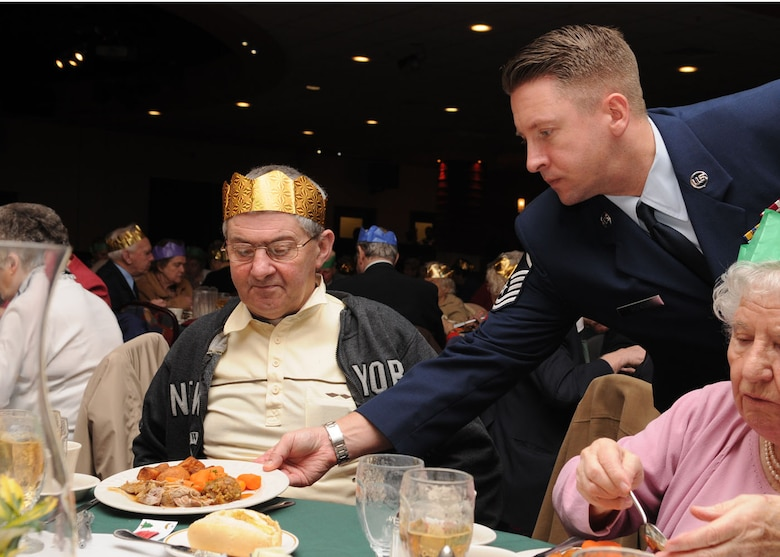 Master Sgt. Matthew Becker from the 100th Maintenance Squadron, serves a hot plate of food to Mr. John Cook from Mildenhall, during the 27th annual Senior Citizens Luncheon Dec. 3, 2008, at RAF Mildenhall, England. Sgt. Matthew's volunteered as an escort to assist the elderly throughout the event. (U.S. Air Force photo by Staff Sgt. Jerry Fleshman)