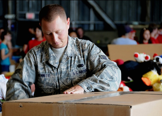 ANDERSEN AIR FORCE BASE, Guam -Senior Airman Craig Bennett, 36th Logistics Readiness Squadron and Operation Christmas Drop Volunteer, prepares a box so it can be filled with goods and supplies here at Hangar 4 Dec. 7. Fishing nets, tools, construction materials, school supplies, shoes, toys and clothing will be dropped in boxes weighing nearly 400 pounds from a C-130 Hercules to aid people of smaller islands that do not have airstrips or major ports. (U.S. Air Force photo by Senior Airman Nichelle Griffiths)