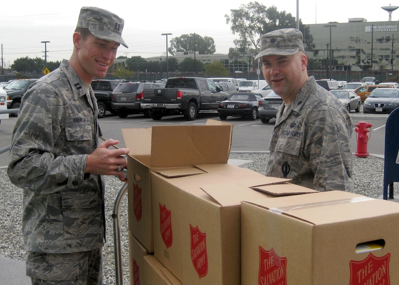 Capt. Garrett Knowlan (left) and Lt. Col. Jon Anderson inspects the boxes full of donated food headed for the Redondo Beach Salvation Army before delivery. (Courtesy photo)
