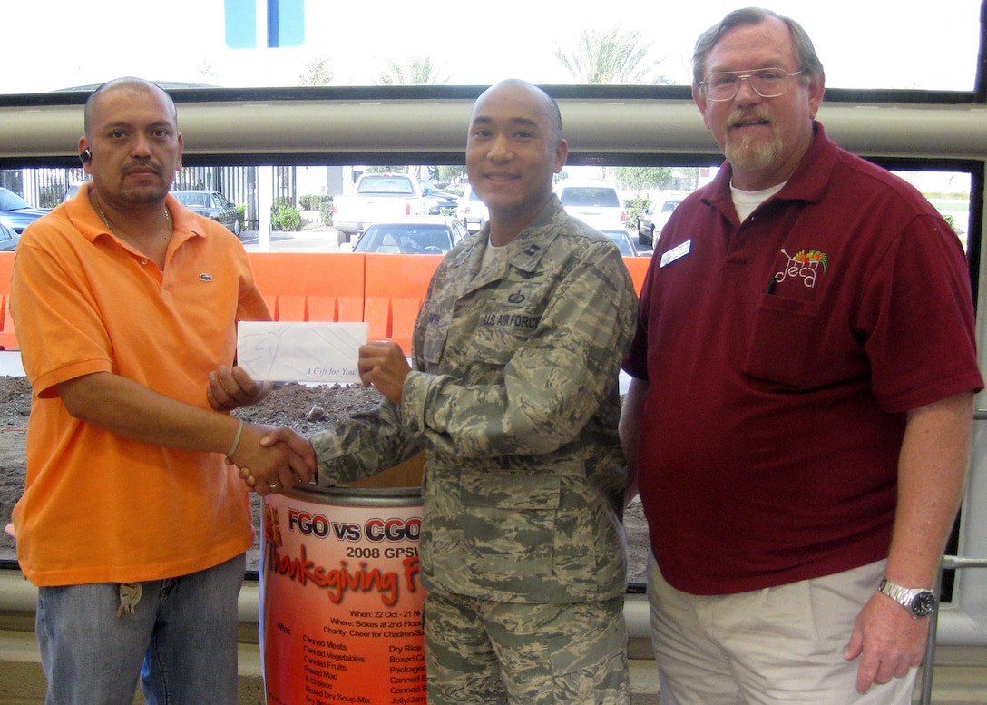 Capt. Trey Smith (center) receives a check for $100 Los Angeles AFB Base Commissary representatives in support of GPSW Thanksgiving Food Drive. (Courtesy photo)