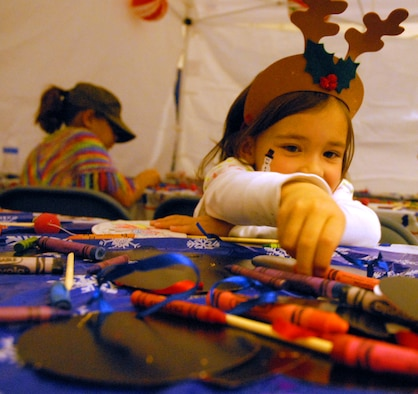 "SCHRIEVER AIR FORCE BASE, Colo. - A child chooses her crayon in the ""crafts booth"" at the Eighth Annual Children's Holiday Festival in the Main Fitness Center here Dec. 6. The festival included games, prizes, food and a visit from Santa and Mrs. Claus. (U.S. Air Force photo/Staff Sgt. Stacy D. Foster)"