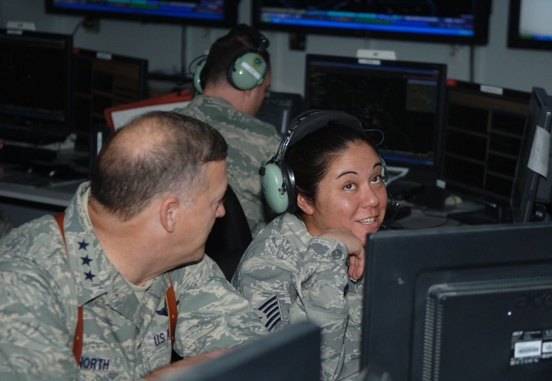 Master Sgt.(s) Jennie Aruda, weapons director, 727 EACS, discusses her role in the CRC with Lt. Gen. Gary North, commander, 9th Air Force during his visit to Joint Base Balad, Iraq.